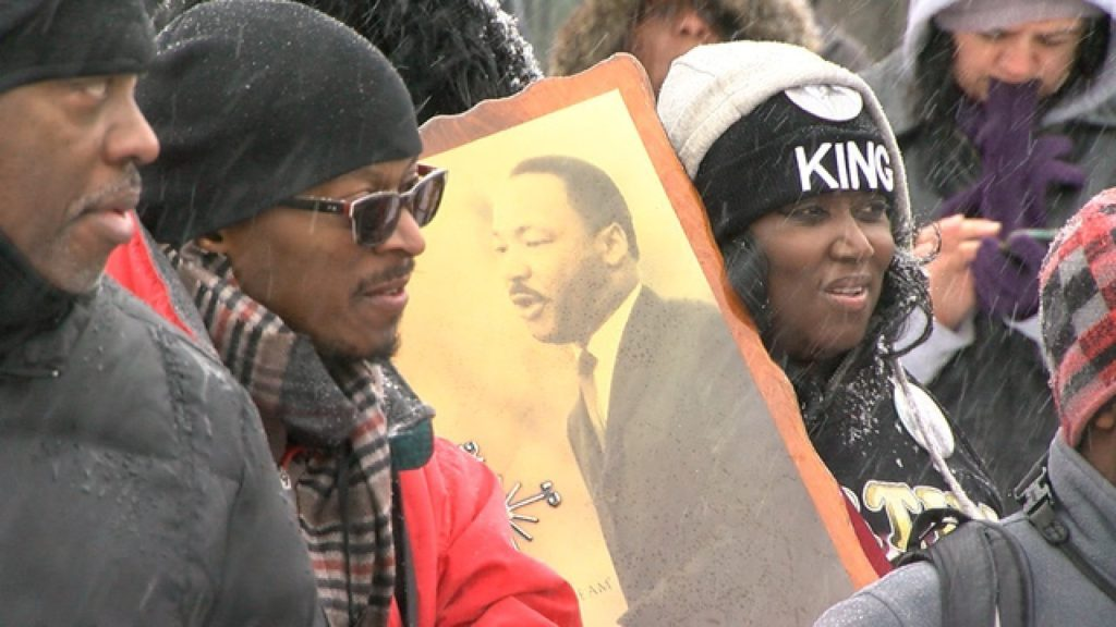 People holding up a picture of Dr. Martin Luther King Jr. as they attend the Marade